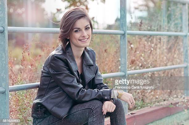Young woman wearing black leather jacket sitting b