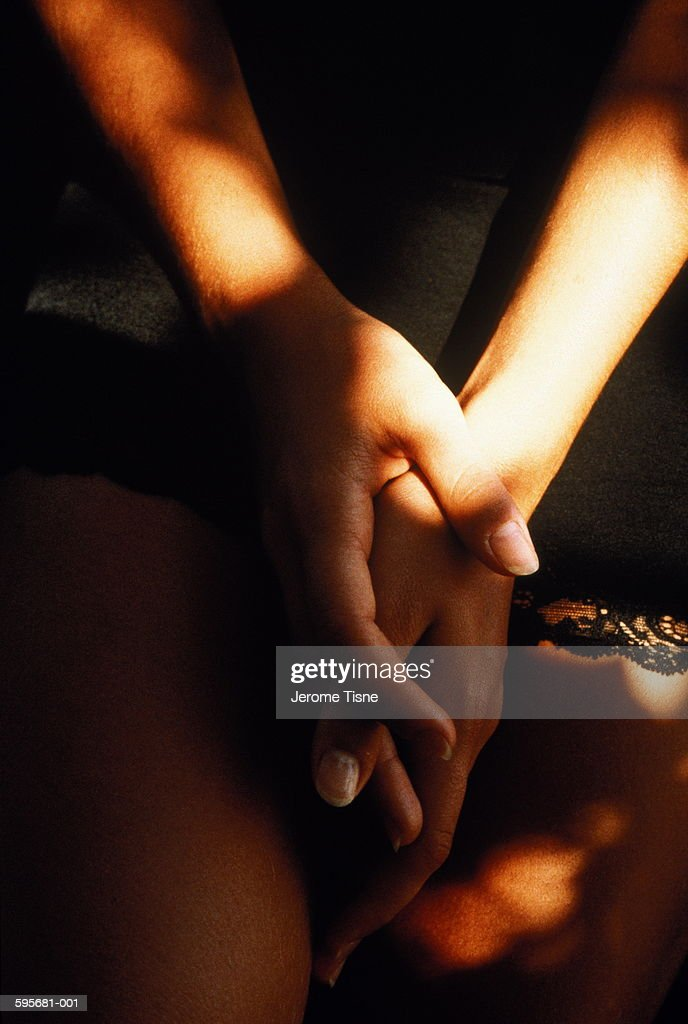 Young woman wearing black lingerie, close-up of hands clasped on lap : Stock Photo