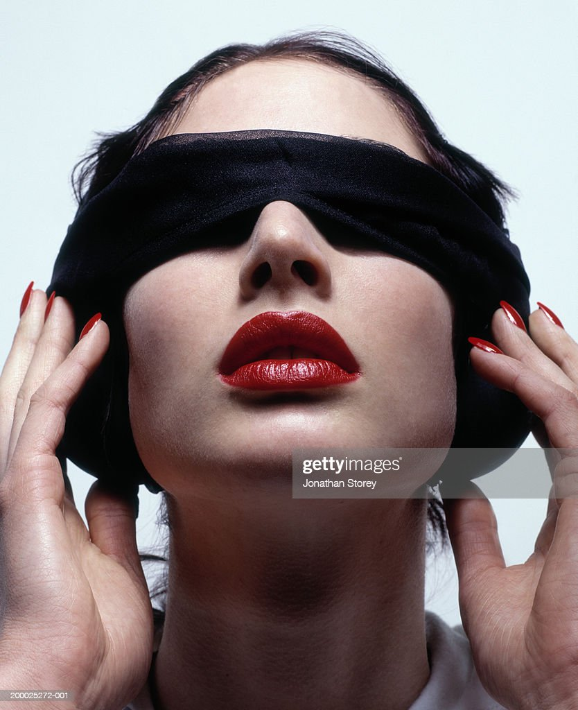 Young woman wearing blindfold, close-up : Stock Photo
