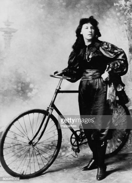 A young woman wearing bloomers poses next to a bicycle circa 1895
