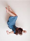 Young woman wearing blue dress falling upside down