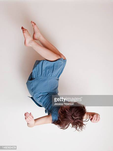 Young woman wearing blue dress falling upside down