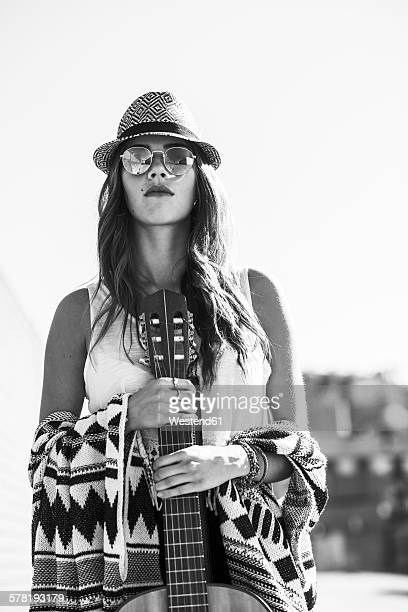Young woman wearing boho style holding guitar