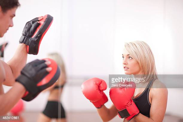Young woman wearing boxing gloves in gym