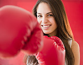 Young woman wearing boxing gloves, smiling
