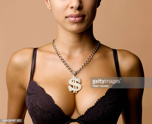 Young woman wearing bra and dollar sign on medallion, mid section
