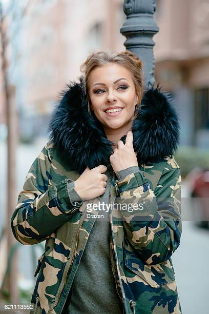 Young woman wearing camouflage military jacket with fur