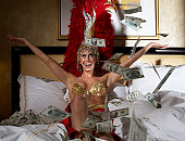 Young woman wearing carnival costume sitting on bed and throwing dollar banknotes into air