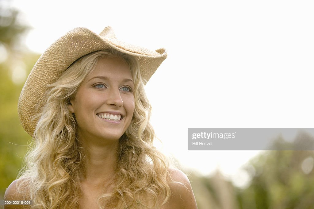Young woman wearing cowboy hat, smiling, looking away
