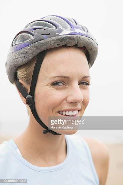 Young woman wearing cycling helmet on beach, portrait