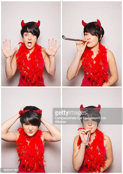 Young woman wearing devil horns in photo booth