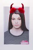 Young woman wearing devil horns