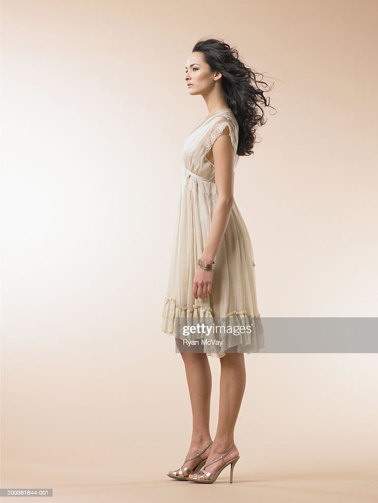Young woman wearing dress, side view : Stock Photo