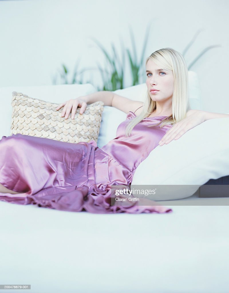 Young woman wearing evening dress relaxing on sofa, portrait : Stock Photo