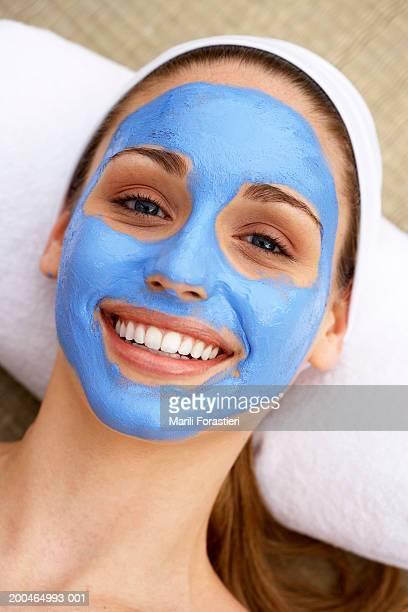 Jeune femme portant un masque du visage souriant, portrait, gros plan
