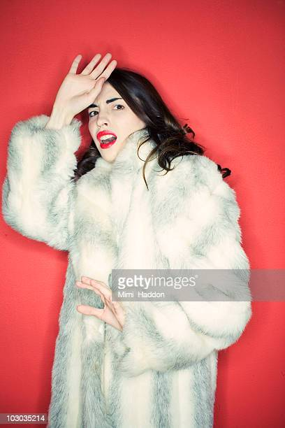 Young Woman Wearing Fur Coat Hiding From Camera