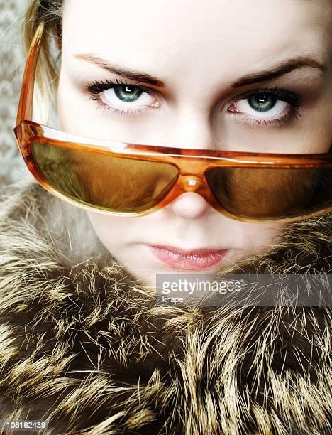 Jeune femme portant Collier en fourrure et des lunettes de soleil