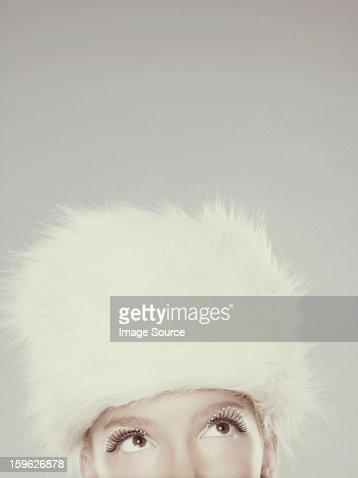 Young woman wearing fur hat and mascara, top section