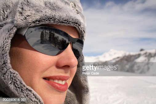 young woman wearing fur hat and sunglasses on ski slopes, side view : Stock Photo