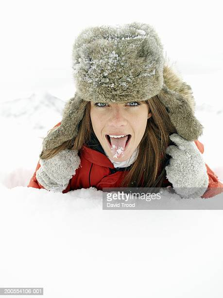 Young woman wearing fur hat, licking ice with tongue, portrait