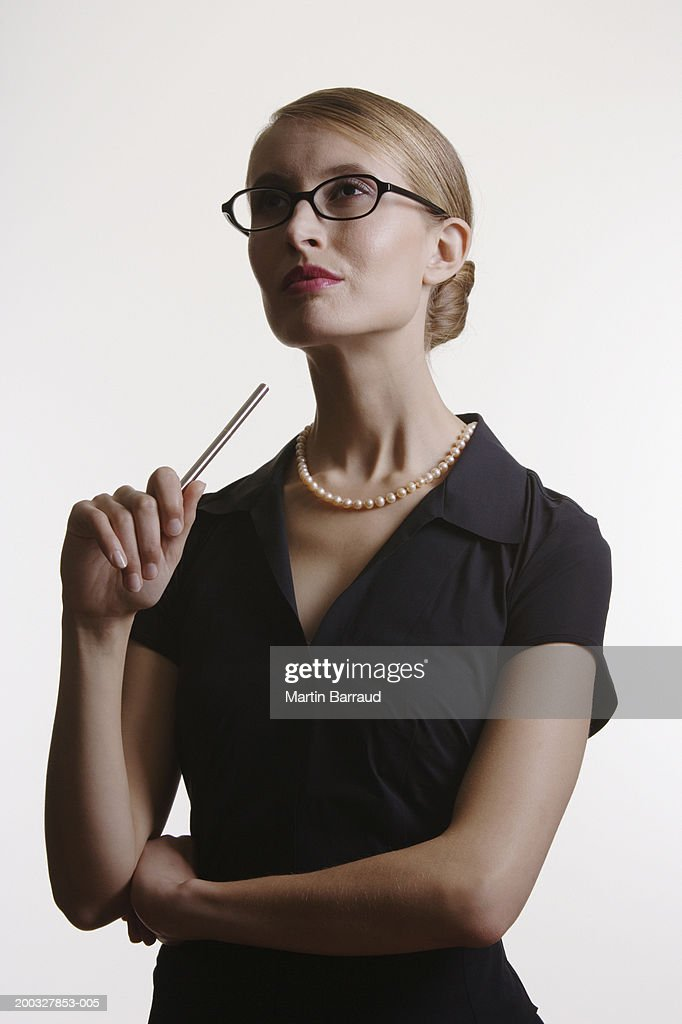 Young woman wearing glasses, holding pen : Stock Photo