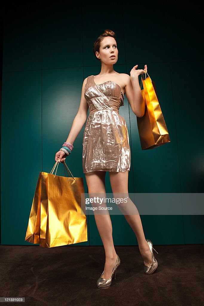 Young woman wearing gold dress with shopping bags, portrait