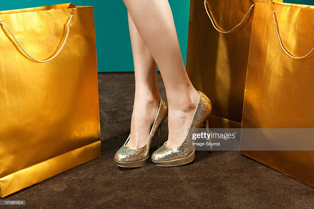 Young woman wearing gold stilettos with shopping bags