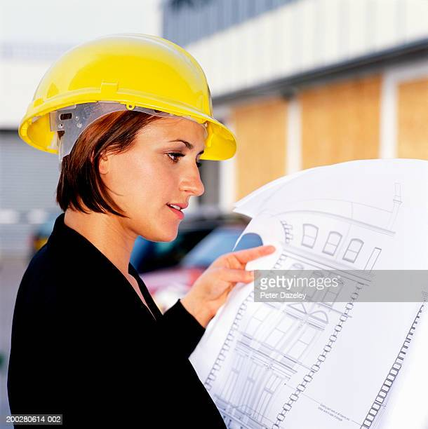 Young woman wearing hardhat, looking at blue prints