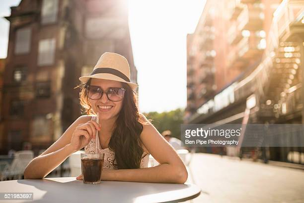 Young woman wearing hat and sunglasses with drink