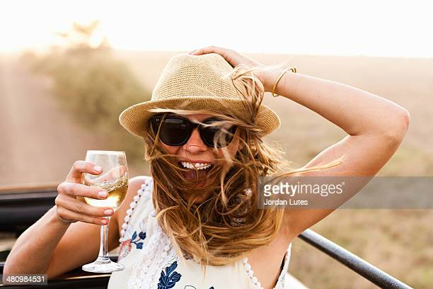 Young woman wearing hat holding glass of wine