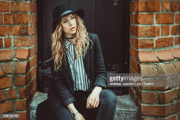 Young Woman Wearing Hat Sitting Against Brick Wall
