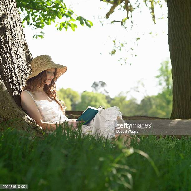 Young woman wearing hat sitting by tree reading book, smiling