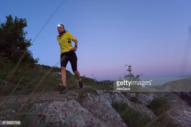 Young woman wearing headlamp trail running in the twilight