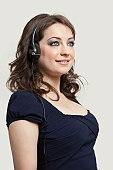 Young woman wearing headphones against gray background