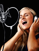 Young woman wearing headphones and singing a song