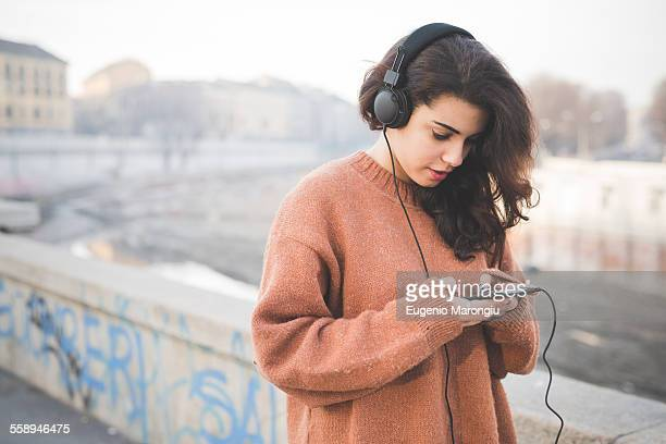Young woman wearing headphones choosing music on smartphone
