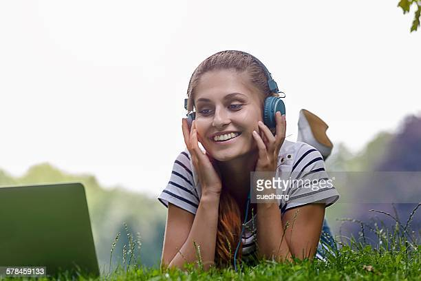 Young woman wearing headphones lying on grass resting on elbows looking at laptop smiling