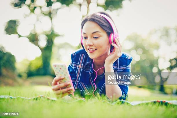 Young woman wearing headphones while holding smart phone in park