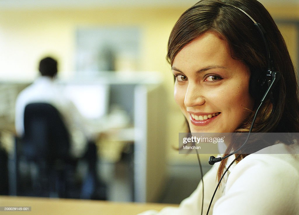 Young woman wearing headset in office, portrait : Stock Photo