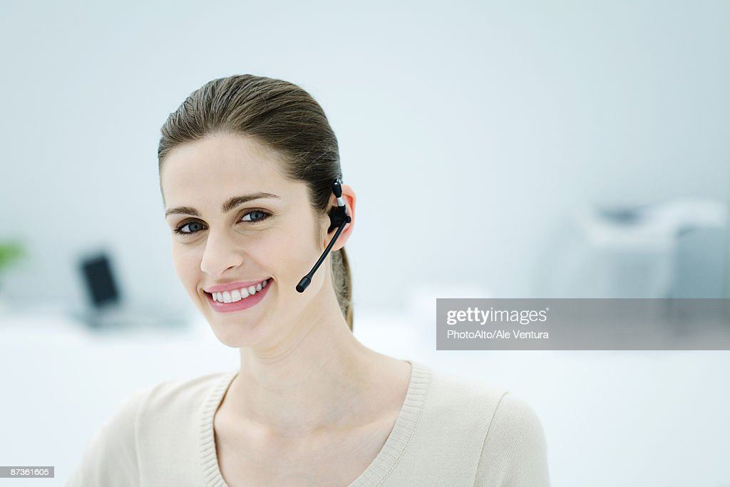 Young woman wearing headset, smiling at camera, portrait
