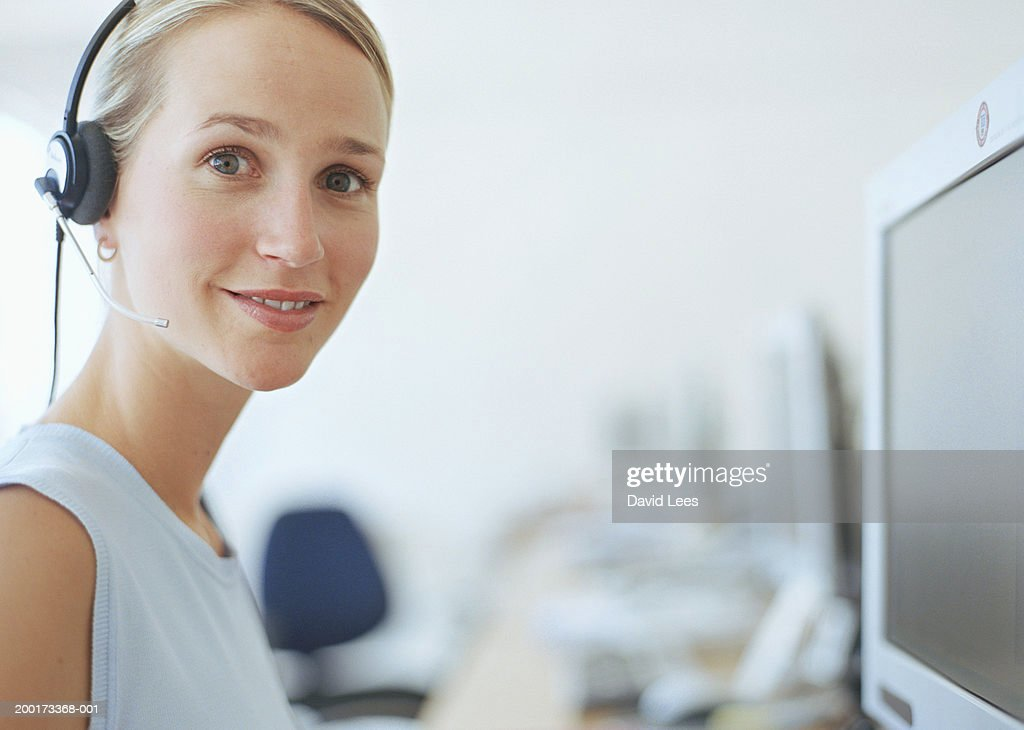 Young woman wearing headset, smiling, portrait, close-up : Stock Photo