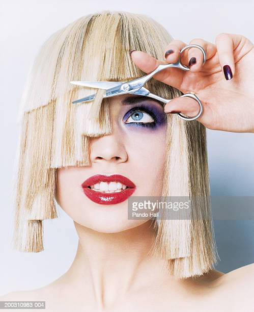 Young woman wearing heavy make-up, cutting uneven hair with scissors