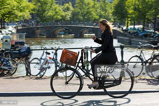 Young woman wearing high heels shoes carrying iPhone cycling out for the evening across bridge in Amsterdam Holland