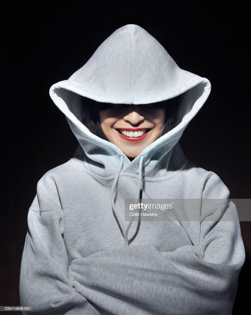 Young woman wearing hooded sweatshirt, portrait : Stock Photo