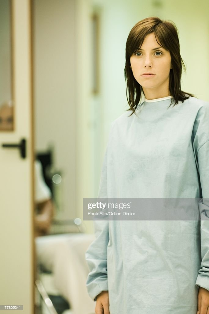 Young woman wearing hospital gown, looking away, hospital corridor in background : Stock Photo