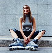 Young woman wearing in-line skates sitting on kerb, smiling, close-up