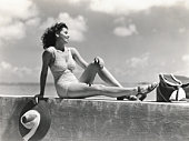 Young woman wearing knitted swimsuit, posing on wall by ocean. (Photo by H. Armstrong Roberts/Retrofile/Getty Images)