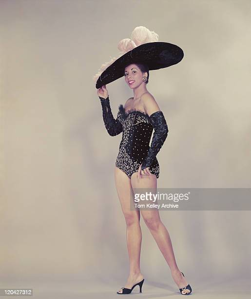 Young woman wearing large dress hat, smiling, portrait