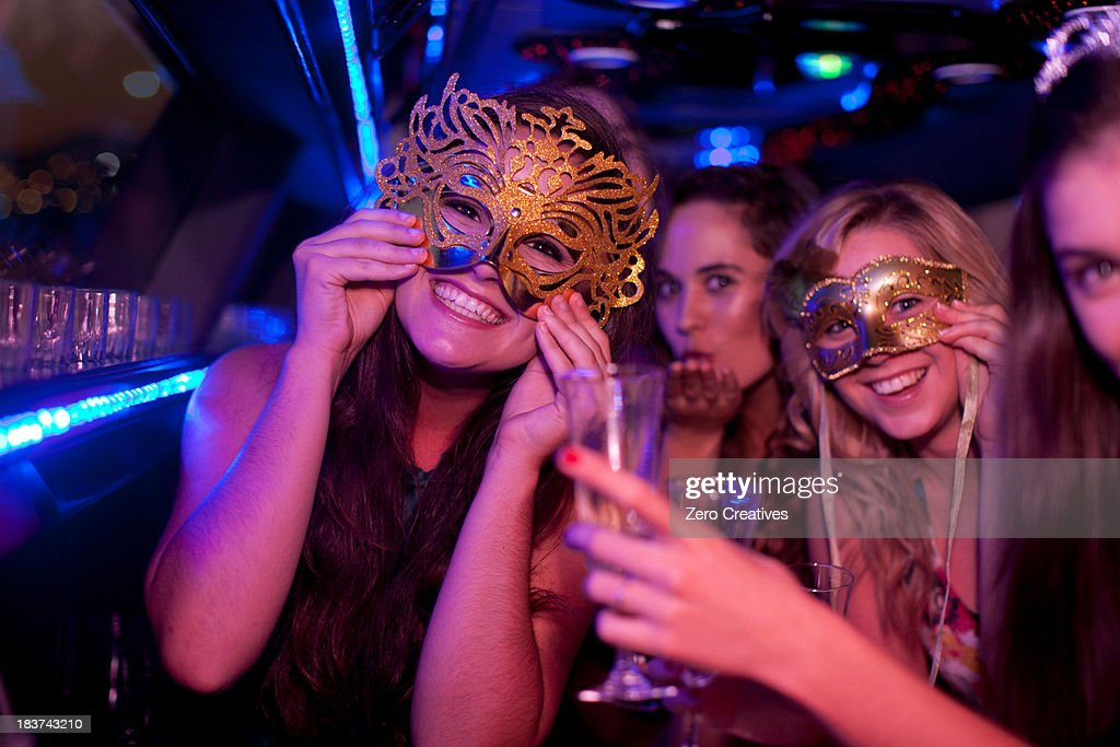 Young woman wearing mask in limousine : Stock Photo