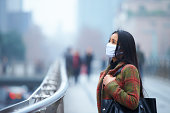 picture of one young asian woman wearing mask in the haze and foggy city.